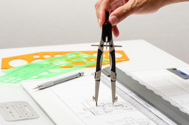 Die hand des nahaufnahmetechnikers während der verwendung der industriellen zeichenwerkzeuge, des industrail-zeichenkonzepts.