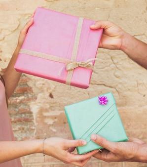 Die hand des paares, die einander valentinsgrußgeschenk gibt
