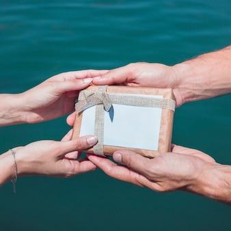 Die hand des paares, die geschenk gegen meerwasserhintergrund hält
