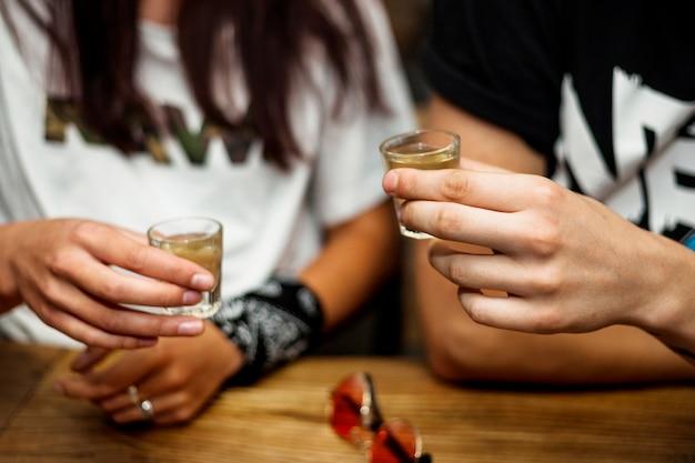 Die hand des paares, die tequila hält, schoss in hände