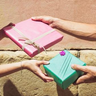 Die hand des paares, die valentinsgrußgeschenk austauscht