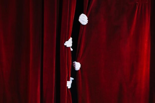 Die hand des pantomimen, die geschlossenen roten vorhang hält