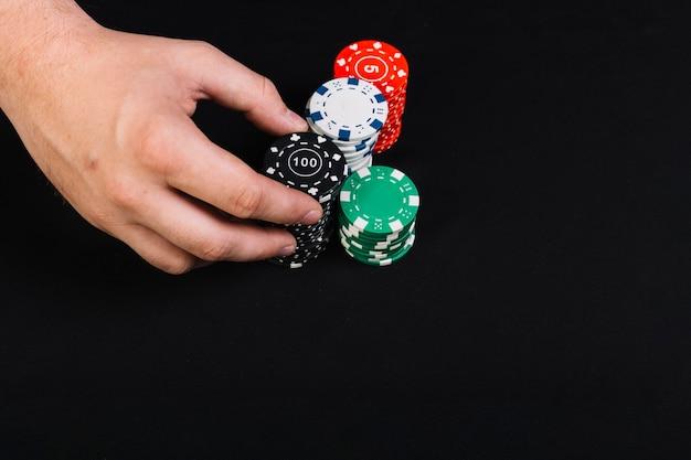 Die hand des pokerspielers, die auf schwarzem hintergrund spielt