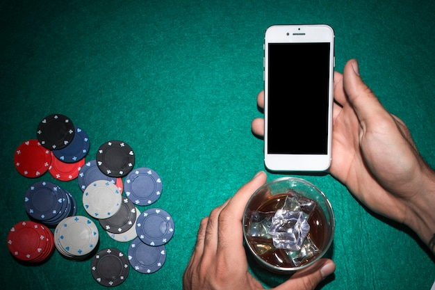 Die hand des pokerspielers, die handy zeigt und whiskyglas auf schürhakentabelle hält