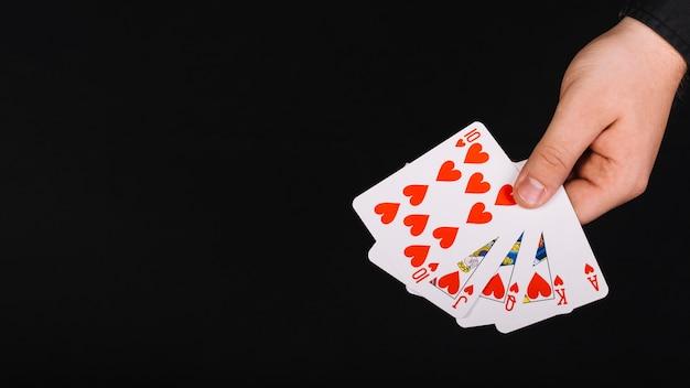 Die hand des pokerspielers mit royal flush-herz auf schwarzem hintergrund