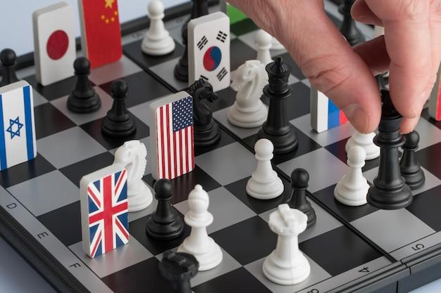 Die hand des politikers bewegt eine schachfigur. konzeptionelles foto eines politischen spiels und einer strategie.