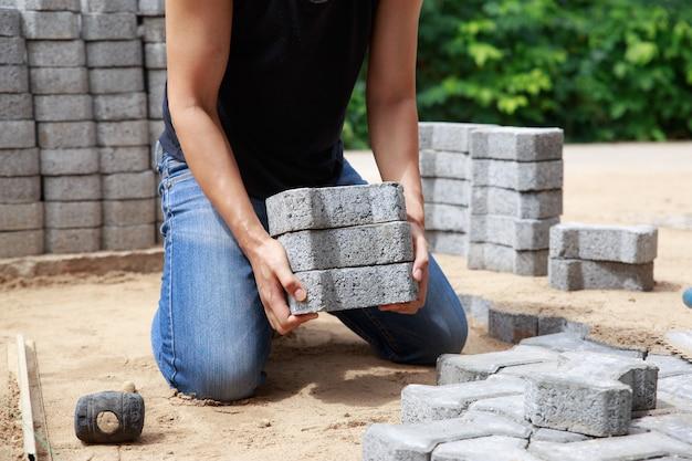 Die hand des professionellen straßenfertigers legt pflastersteine in schichten für weg-, arbeits- und industriekonzept.