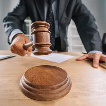 Die hand des rechtsanwalts, die hölzernen hammer auf klingendem block schlägt