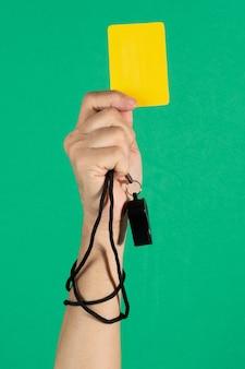 Die hand des schiedsrichters hält eine gelbe karte und pfeift auf grünem hintergrund.