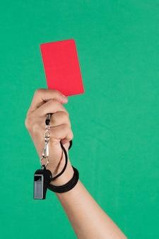 Die hand des schiedsrichters hält eine rote karte und pfeift auf grünem hintergrund.