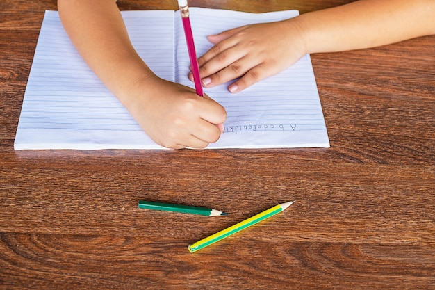 Die hand des schülers ist auf dem schultisch auf papier geschrieben.