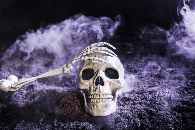 Die hand des skeletts, die schädel im nebel auf dem boden berührt