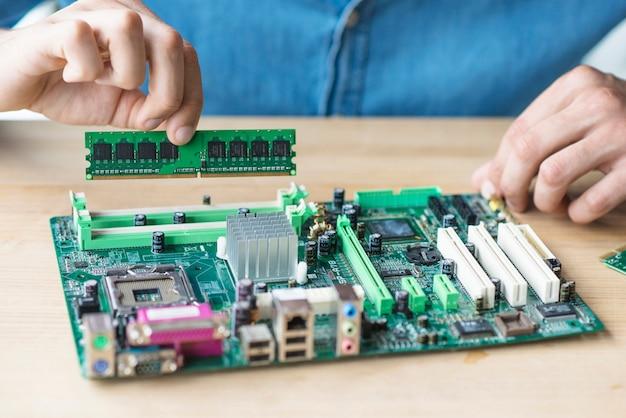 Die hand des technikers, die ram hält, motherboard reparierend