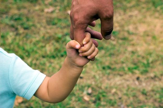 Die hand des vaters führen seinen kindersohn in der sommerwaldnatur im freien, vertrauen familienkonzept