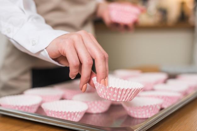 Die hand des weiblichen bäckers, die den kasten des kleinen kuchens auf das fach setzt
