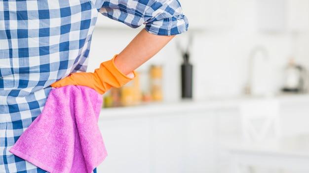 Die hand des weiblichen hausmeisters auf der hüfte, die rosa serviette hält