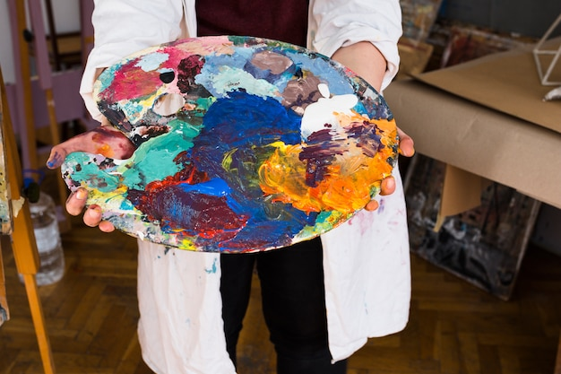 Die hand des weiblichen künstlers, die unordentliche farbpalette zeigt