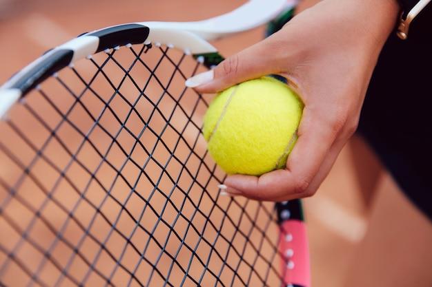 Die hand des weiblichen spielers mit dem tennisball, vorbereitend, während eines spiels zu dienen