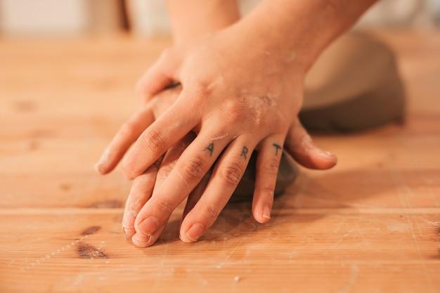Die hand des weiblichen töpfers, die den lehm auf holzoberfläche knetet