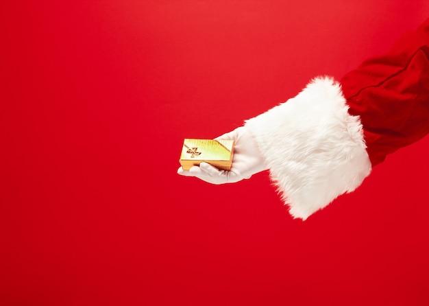 Die hand des weihnachtsmannes, der ein geschenk auf rotem hintergrund hält. die jahreszeit, winter, feiertag, feier, geschenkkonzept