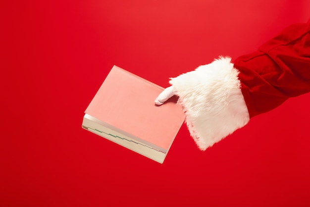 Die hand des weihnachtsmannes, der ein notizbuch auf rot hält