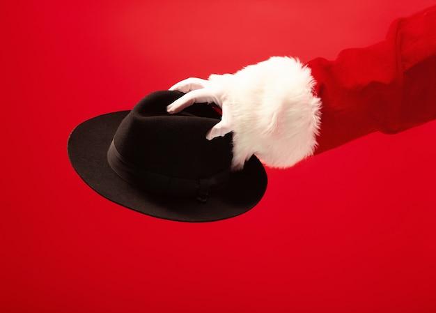 Die hand des weihnachtsmannes, der einen schwarzen hut auf rotem hintergrund hält. die jahreszeit, winter, feiertag, feier, geschenkkonzept