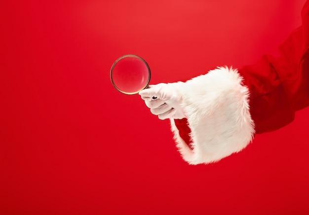 Die hand des weihnachtsmannes hält eine lupe auf rot