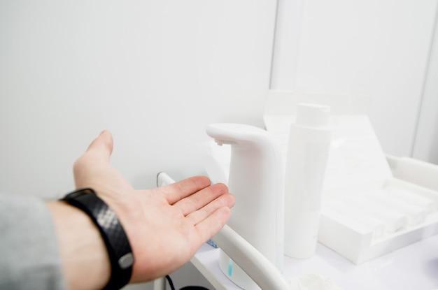 Die hand des weißen mannes wird vor dem arztbesuch gereinigt