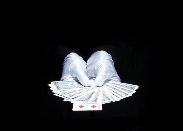 Die hand des zauberers, die aufgelockertes plattform der spielkarte gegen schwarzen hintergrund zeigt