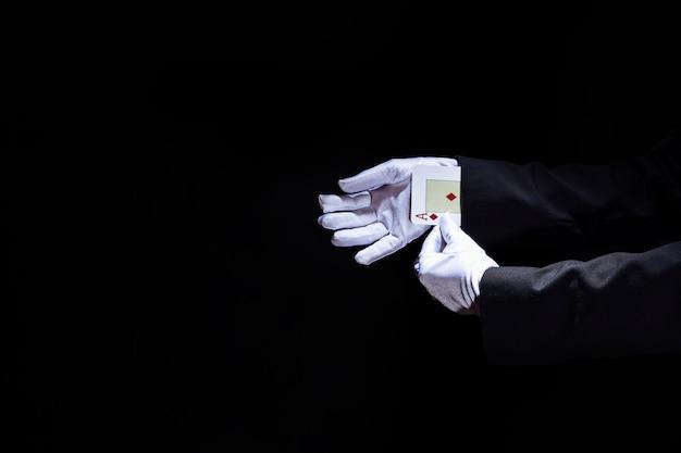 Die hand des zauberers, die spielkarte der asse vom ärmel gegen schwarzen hintergrund entfernt