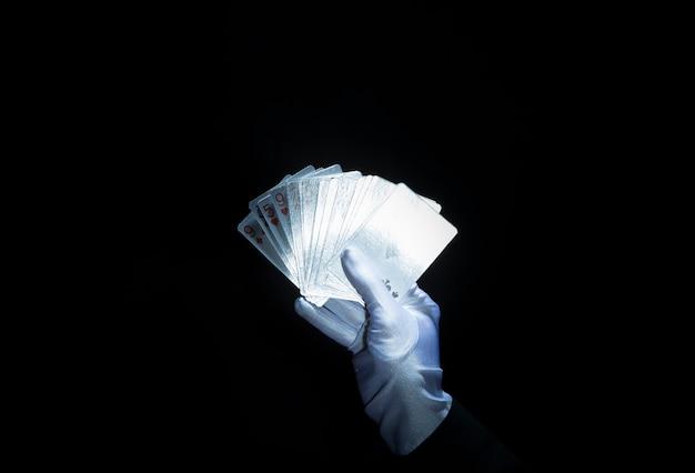Die hand des zauberers tragender weißer handschuh, der aufgelockerte spielkarten gegen schwarzen hintergrund hält