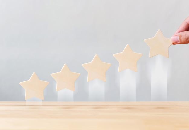 Die hand, die das wachsende wachstum der hölzernen form mit fünf sternen hält, erhöhen qualität auf tabelle. das beste konzept für die bewertung des kundenerlebnisses durch exzellente unternehmensdienstleistungen