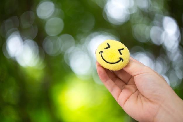 Die hand, die den smiley emoticon hält, um ermutigung zu geben