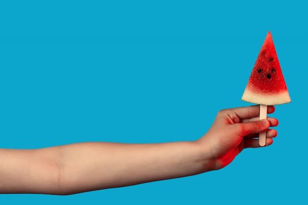 Die hand, die ein stück wassermelone auf einem stock hält, mögen eiscreme auf blau