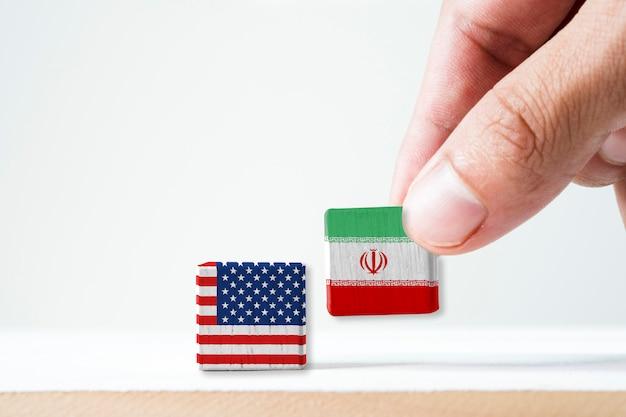 Die hand, die hölzernen kubik des druckbildschirms iran-flagge und usa-flagge setzt. es ist symbol von vereinigten staaten von amerika und der iran haben konflikt in den atomwaffen und in der straße von hormus