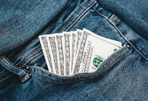 Die hand, die in ihre jeans-tasche für 100 us-dollar steckt.