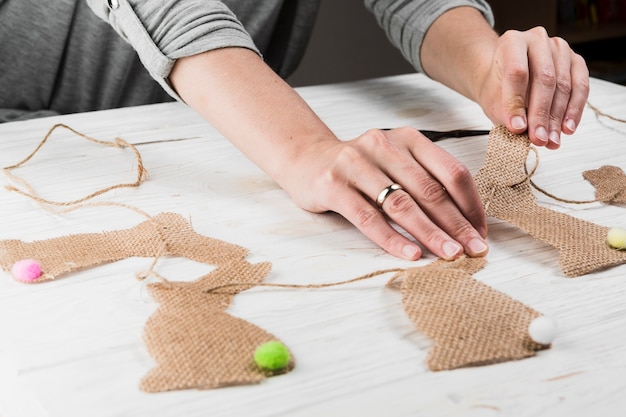 Die hand, die kaninchenformflagge vom jutefaser macht, kleidet auf tabelle
