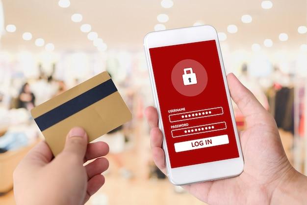 Die hand, die kreditkarte und intelligentes telefon mit passwort hält, melden sich auf schirm für das einkaufen onlin an