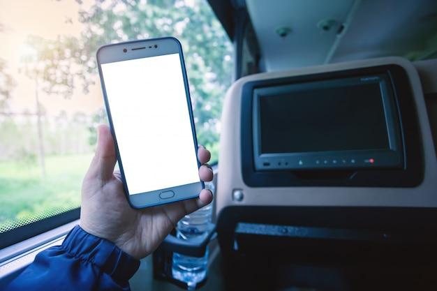 Die hand, die smartphone unscharfe bilder hält, berühren für unterhaltung den bus unscharfen hintergrund