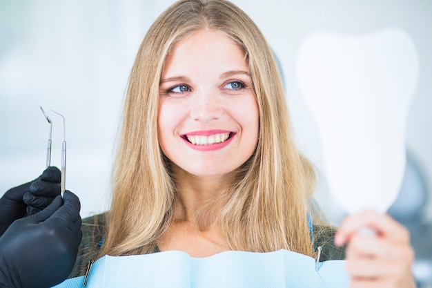 Die hand doktors, die werkzeuge hält, nähern sich lächelndem weiblichem patienten