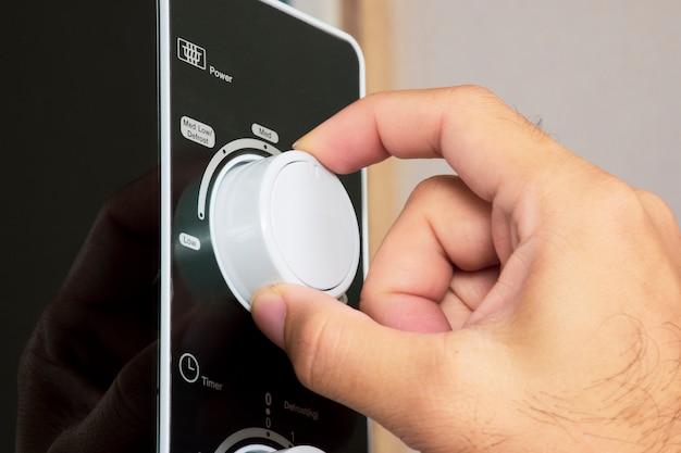Die hand dreht den moduswahlschalter des mikrowellenknopfs