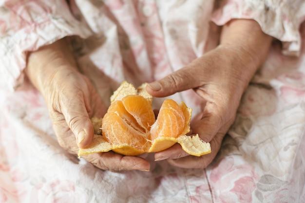 Die hand einer alten frau schält eine chinesische orange