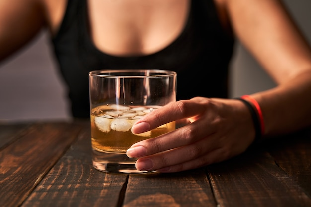 Die hand einer betrunkenen frau, die ein glas alkohol hält. konzept von alkoholismus und sucht.