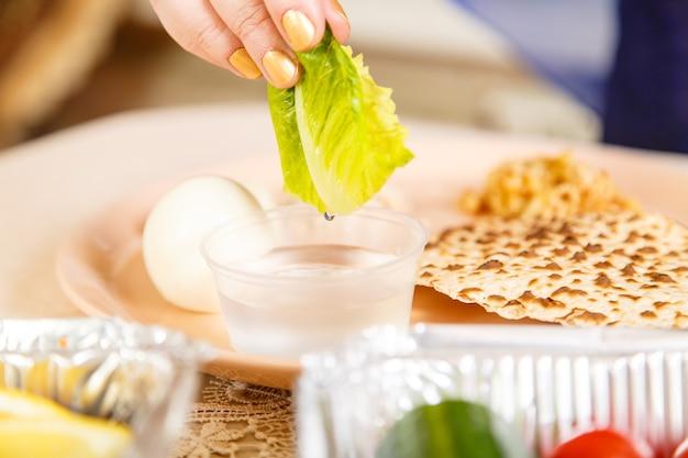 Die hand einer frau am osterseder-tisch taucht maror und karpas in salzwasser. horizontales foto