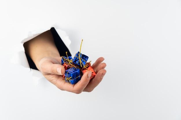 Die hand einer frau bricht durch eine weiße wand, auf ihrer handfläche befinden sich rote und blaue geschenke. es gibt einen urlaub hinter der mauer. speicherplatz kopieren