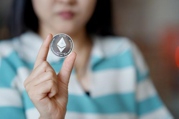 Die hand einer frau, die eine ethereum-münze hält neues konzept kryptowährung virtuelles geld
