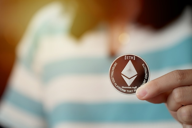 Die hand einer frau, die eine ethereum-münze hält
