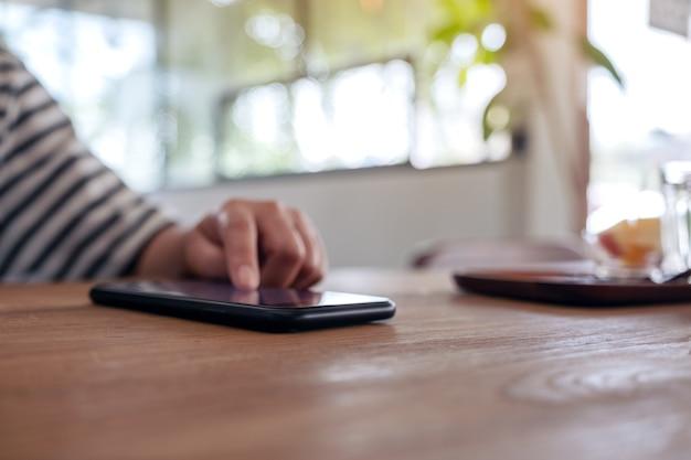 Die hand einer frau, die einen smartphonebildschirm auf holztisch benutzt und berührt