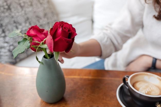 Die hand einer frau, die rote rosenblume in einer grünen vase anordnet