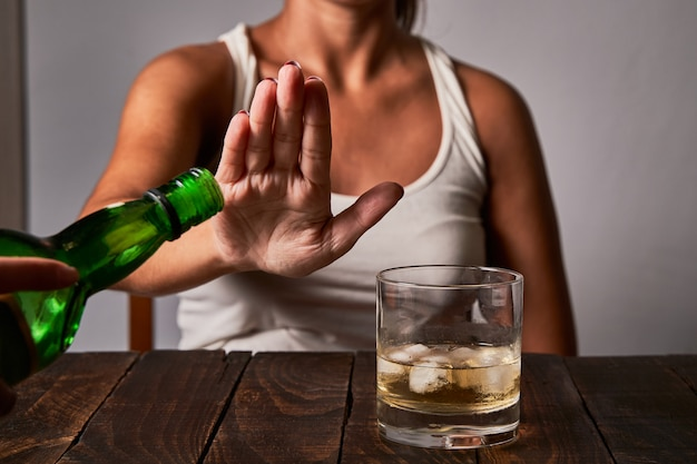 Die hand einer frau, die sagt, gib kein getränk mehr in ihr glas. konzept des alkoholismus und nicht trinken, um zu fahren.